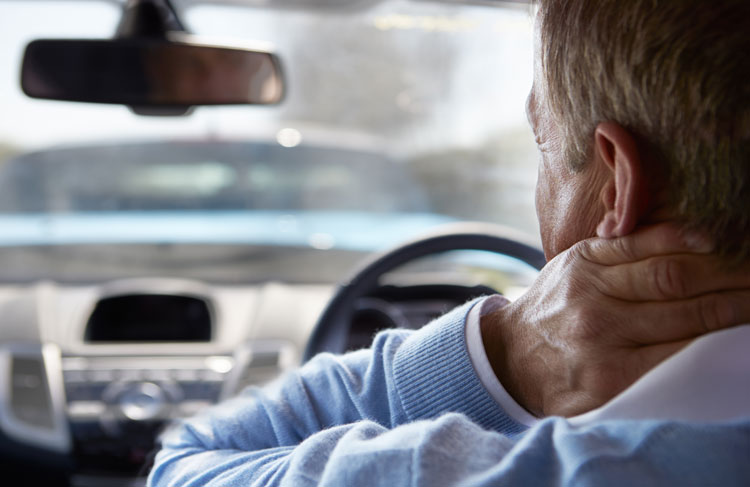 man in car with whiplash