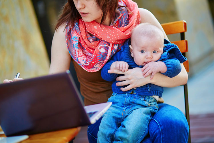 young mum with baby on laptop
