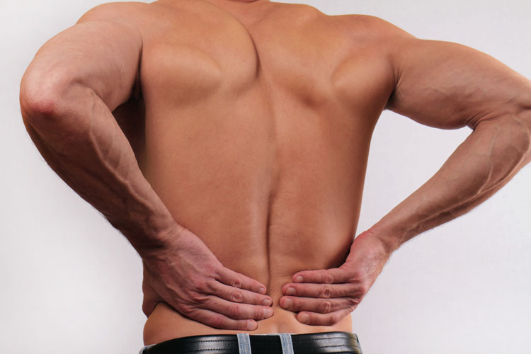 man with lower back pain holding his back
