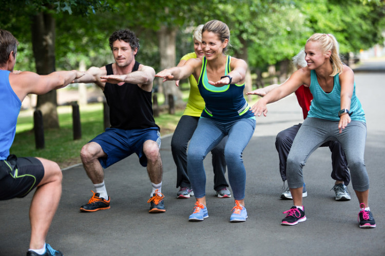 fitness group doing squats in the park